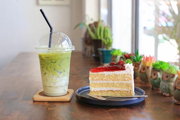 De aardbeicake in metaaldienblad en bevroren matcha groene thee latte haalt binnen kop op houten lijst bij koffie weg.