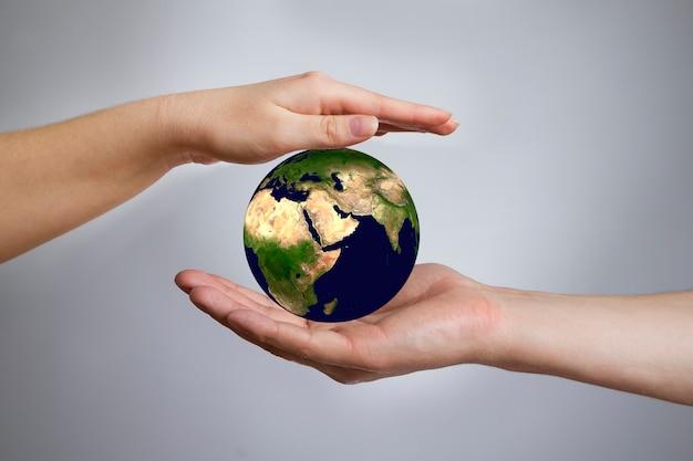 De aarde in vrouwelijke en mannelijke handen. 3d render
