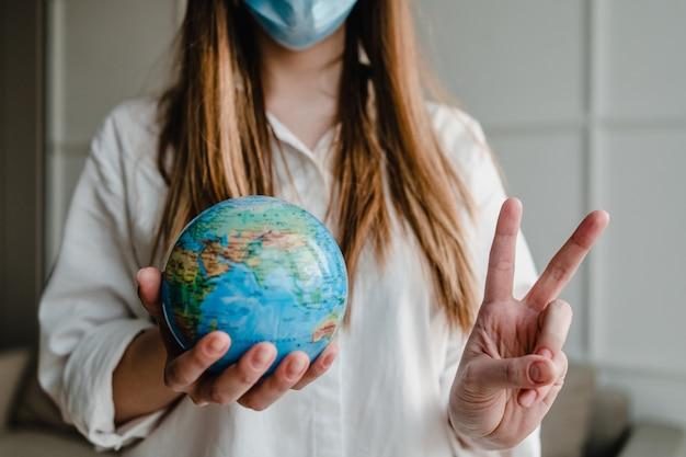 De aardebol die van de vrouwenholding thuis masker dragen die vredesgebaar tonen