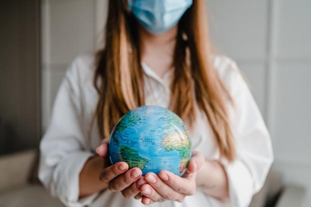 De aardebol die van de vrouwenholding thuis masker dragen