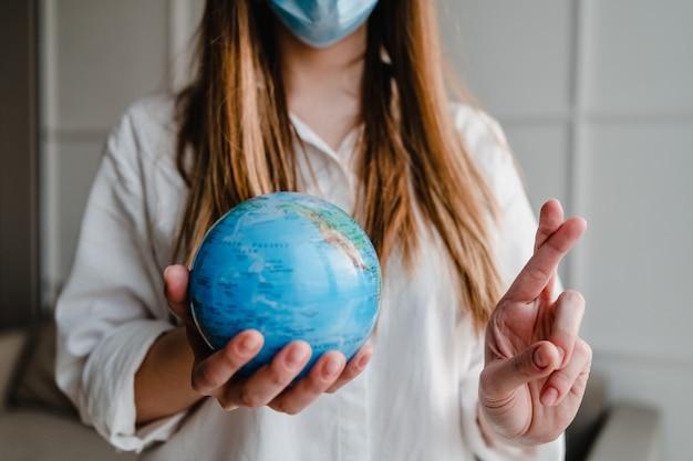De aardebol die van de vrouwenholding thuis thuis gekruiste vingers van de maskerholding dragen