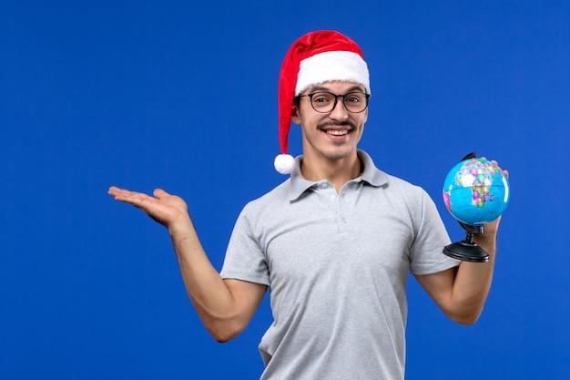 De aardebol van de vooraanzicht de jonge mannelijke holding op de menselijke vakantiereis van het blauwe muurvliegtuig