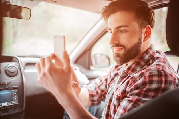 De aardige kerel neemt foto van zijn partner op de witte telefoon. hij kijkt naar het scherm en lacht een beetje.