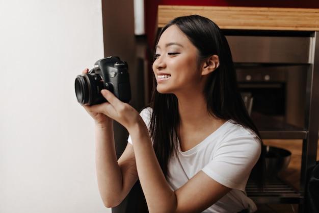 De aardige vrouw in witte bovenkant glimlacht en neemt foto's op voorzijde