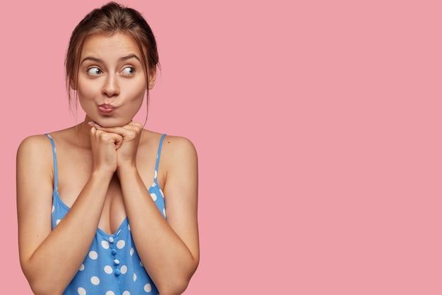 De aarzelende europese jonge vrouw beft lippen