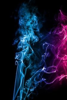 De abstracte blauwe roze gekleurde rook stroomde op zwarte achtergrond.