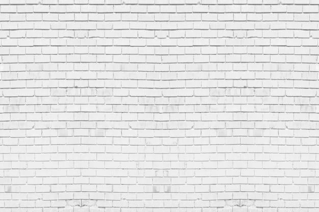 De abstracte doorstane textuur bevlekte oude lichtgrijs gipspleister. witte bakstenen muurachtergrond in landelijke ruimte.