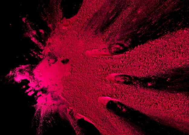 De abstracte explosie van het roze kleurenpoeder over zwarte achtergrond