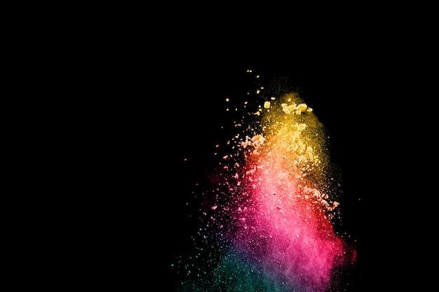 De abstracte explosie van het veelkleurige poeder op zwarte achtergrond.