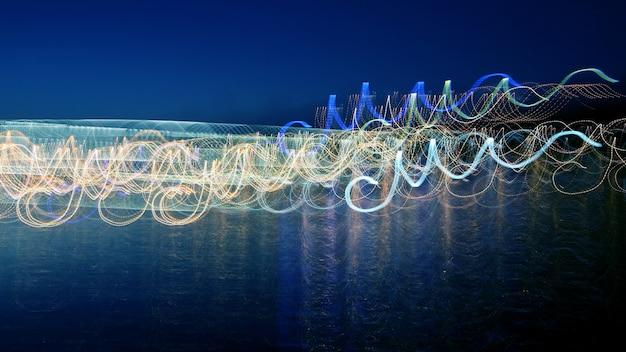 De abstracte gekleurde golven van verlichting in de reflectie over het water. abstractie en vaagheid in de natuur