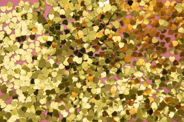 De abstracte geweven backgraund, gouden hartvorm schittert over roze achtergrond. valentijnsdag, liefde, verjaardag, feestconcept.