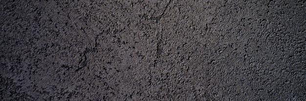 De abstracte geweven donkergrijze of zwarte ruwe achtergrond van de oppervlaktetextuur, cementbetonnen vloer of muur. banner