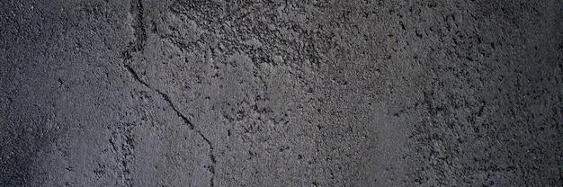 De abstracte geweven donkergrijze of zwarte ruwe achtergrond van de oppervlaktetextuur, cementbetonnen vloer of muur