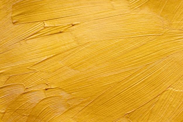 De abstracte gouden verfborstel strijkt textuurachtergrond