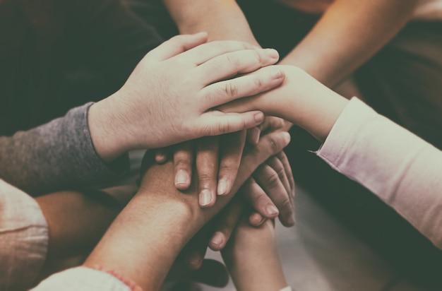 De abstracte kunst van de handen van volwassenen en kinderen op elkaar gestapeld, medewerker, vakbond, lid worden van teamwerk