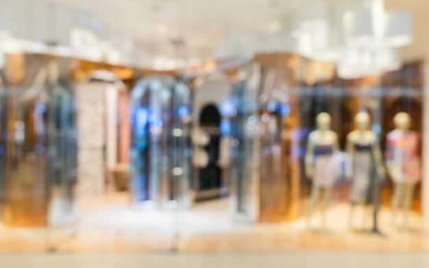 De abstracte onscherpe moderne opslag van manierkleren in een luxewinkelcomplex voor achtergrond, die het winkelen concept kleden.
