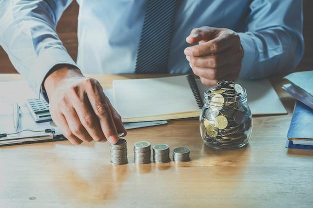 De accountant berekent geldmuntstukken op lijst in bureau. concept financiën en boekhouding