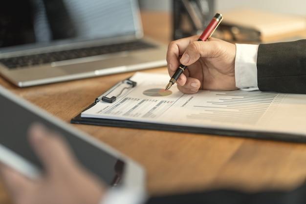 De accountant controleert documenten over grafiek en grafiek met betrekking tot financiële rapportering en belastingadministratie van het bedrijf