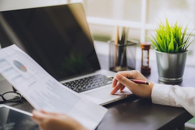 De accountant die documenten over grafiek controleert en financiële en belasting in kaart brengt
