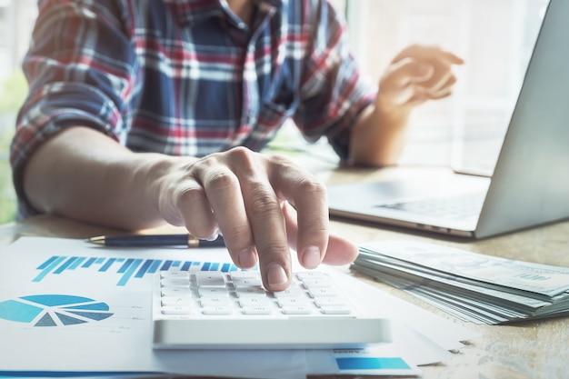 De accountant drukt op de rekenmachine om de juistheid van het investeringsbudget te controleren