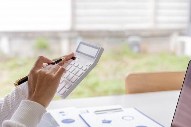 De accountant drukt op de witte rekenmachine, zij is de accountant van het bedrijf die verantwoordelijk is voor het controleren van alle inkomsten en uitgaven van het bedrijf op juistheid. boekhoudkundig controleconcept.