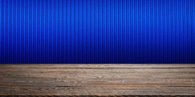 De achtergrond is blanco houten planken en een getextureerde gestreepte muur met gradiëntverlichting en vignettering. voor productdemonstraties, vrije ruimte, lay-out, mockup, perspectiefbord, achtergrondbord.