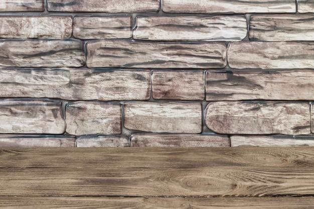 De achtergrond is een muur van grote bruine bakstenen en houten planken.