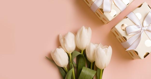 De achtergrond is feestelijk. geschenken in witte verpakking naast bloemen. kopieer ruimte. uitzicht van boven