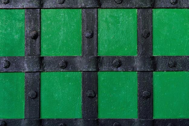De achtergrond is geverfd met groene verf met metalen balken en klinknagels.
