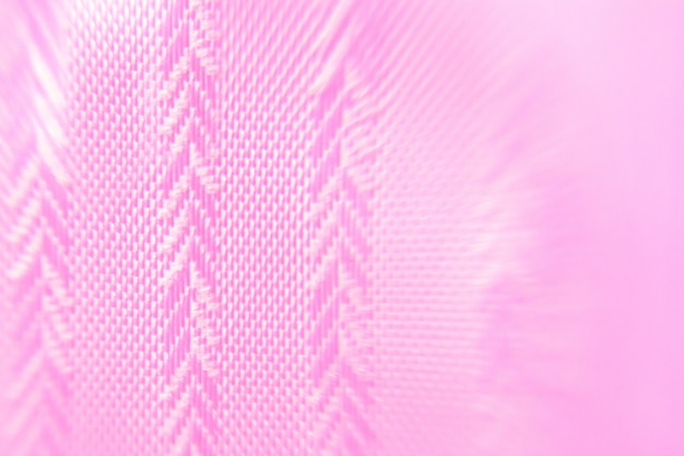 De achtergrond is roze met een geometrische textuur van stof in de vorm van vuren