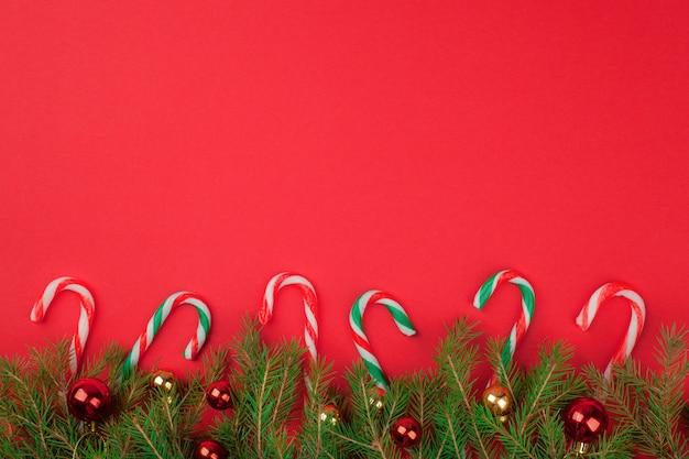 De achtergrond van de kerstboomspar met suikergoedriet en ballen. bovenaanzicht