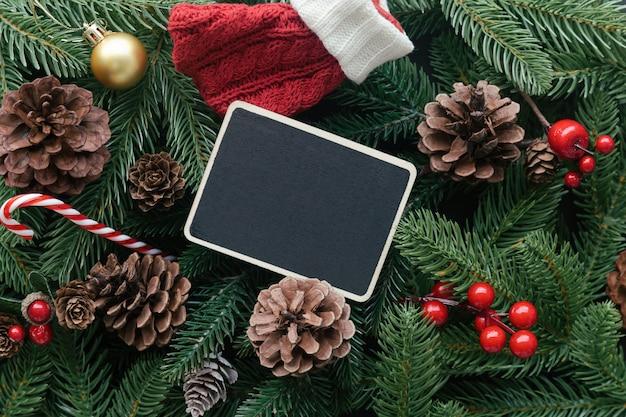 De achtergrond van de kerstmisdecoratie met pijnboombladeren, denneappels, hulstballen, snoep kan, rode sok en lege houten plankkaart