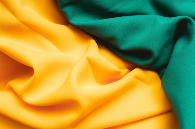 De achtergrond van de stoftextuur met groene en gele kleuren die de kleuren van de braziliaanse vlag herinneren