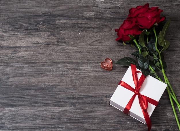De achtergrond van de valentijnskaartendag, de kaart van de valentijnskaartendag met rozen en giften op houten raad