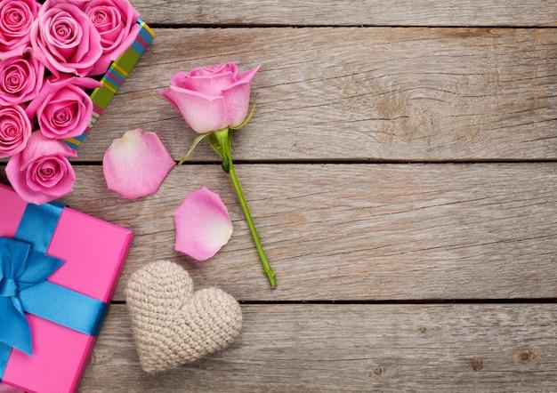 De achtergrond van de valentijnskaartendag met de dooshoogtepunt van roze rozen en handmaded stuk speelgoed hart