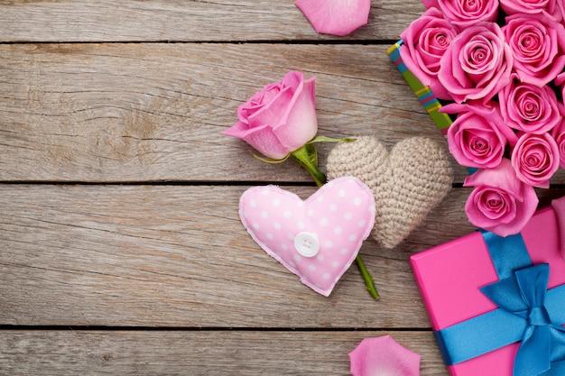 De achtergrond van de valentijnskaartendag met de dooshoogtepunt van roze rozen en handmaded stuk speelgoed harten