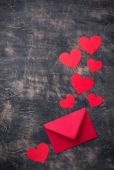 De achtergrond van de valentijnskaartendag met envelop en document harten