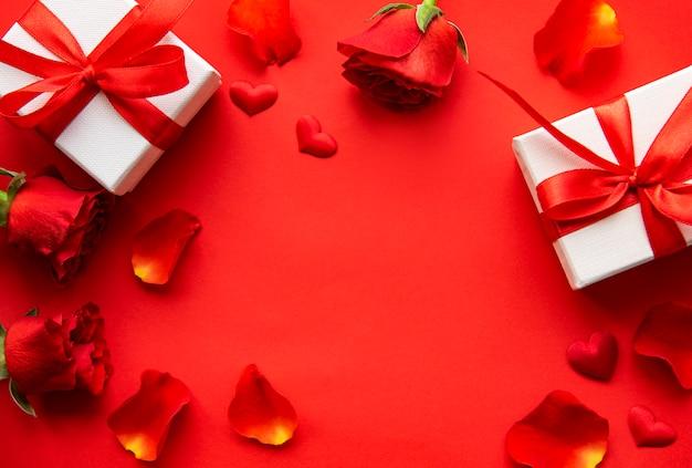 De achtergrond van de valentijnskaartendag met giftdozen, rode rozen en bloemblaadjes