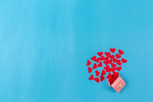 De achtergrond van de valentijnskaartendag met rode hart en giftdoos op blauwe achtergrond.