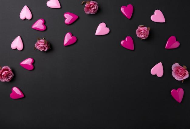 De achtergrond van de valentijnskaartendag met rode harten en nam op zwarte exemplaar ruimteachtergrond toe.