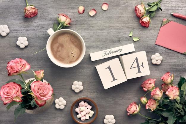 De achtergrond van de valentijnskaartendag met roze rozen, houten kalender, groetkaart en decoratie