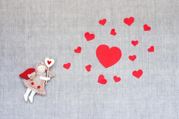 De achtergrond van de valentijnskaartendag met stuk speelgoed de fee van de ambachtengel en vele rode vorm van de hartenwolk
