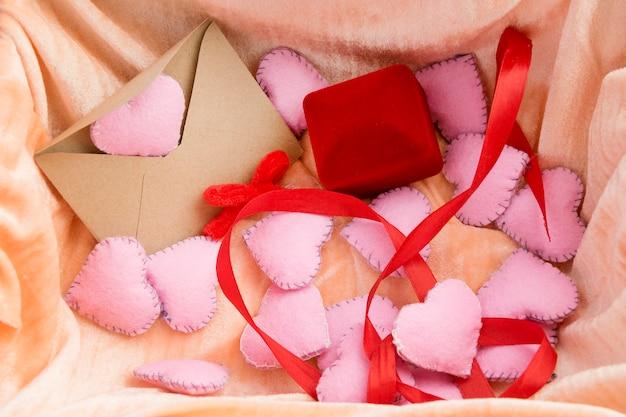 De achtergrond van de valentijnskaartendag met trouwringvakje en liefdebrief.