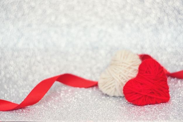 De achtergrond van de valentijnskaartendag, mockup met twee rood gebreid pluizig hart