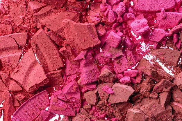 De achtergrond van gebroken roze bloost kosmetisch poeder