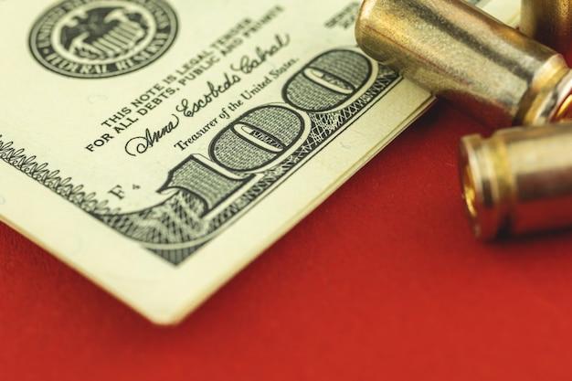 De achtergrond van het criminele geldconcept, close-up honderd rekening en kogel, foto van de pistoolpatroon