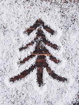 De achtergrond van het kerstmisconcept, geschilderde boom op witte sneeuw, vakantiesymbool.