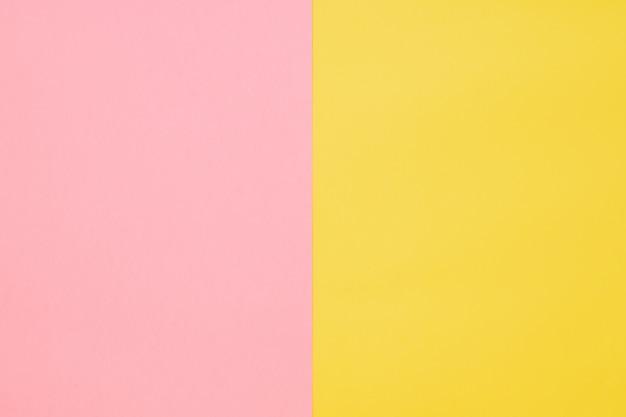 De achtergrond van het papier is geel en roze. vlakke stijl. modieuze kleur.