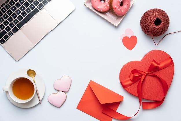 De achtergrond van het valentijnskaartendesktop met rode hartgift, laptop en thee. valentijnsdag wenskaart.
