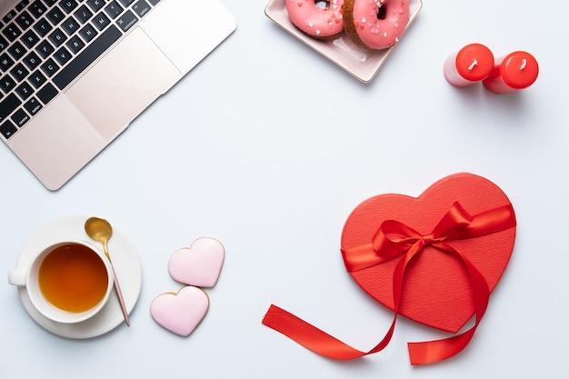 De achtergrond van het valentijnskaartendesktop met rood hartgift, laptop en thee. valentijnsdag wenskaart. vrouwelijke werkplek. bovenaanzicht
